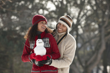 Couple making small snowman