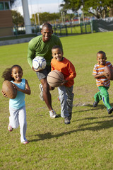 African American father playing ball with children