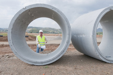 Hispanic worker standing near large cement pipes
