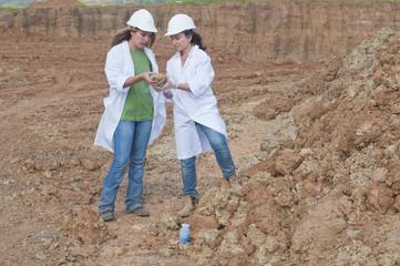Workers analyzing rock specimen