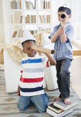 Boys playing with paper hats and cardboard telescopes