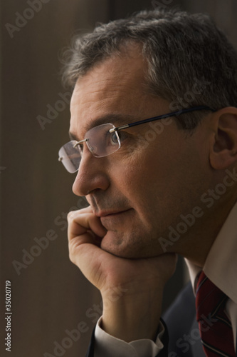 Serious Caucasian businessman with hand on chin