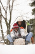 African American couple sledding on snowy hill