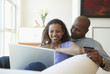 Couple using laptop together on sofa