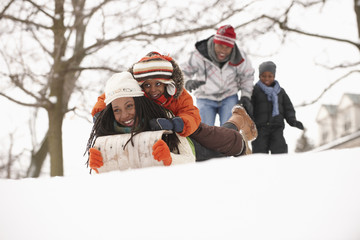 African American family sledding on snowy hill