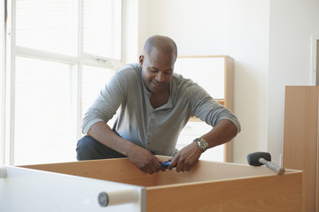 African American man assembling cabinet