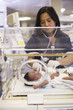 Nurse helping newborn baby in hospital nursery