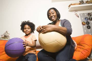 African American mother and son holding balls