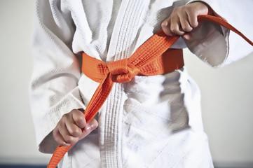 African American boy tightening karate belt