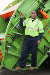 Black man riding on back of garbage truck