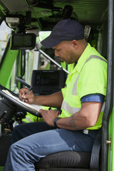 African American man in garbage truck writing on clipboard