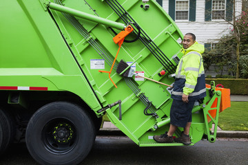 Pacific Islander man riding on garbage truck