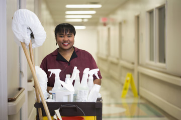 Janitorial worker with cart in hospital hallway