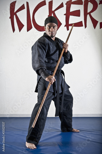 African American man practicing karate with stick