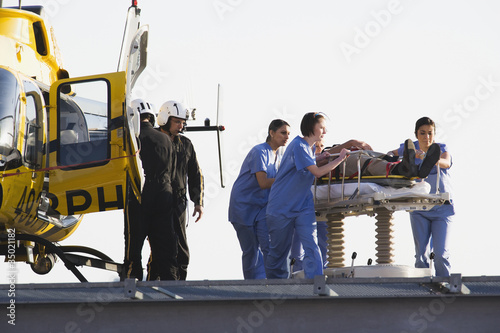 Medical personnel rushing patient from helicopter