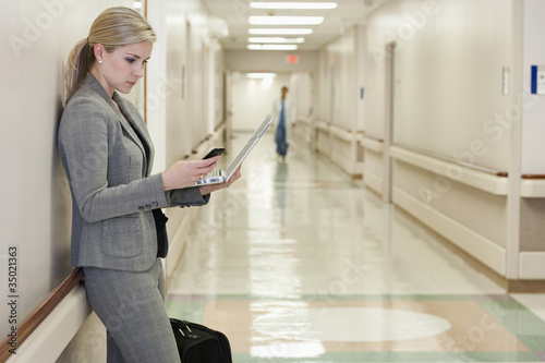 Caucasian businesswoman using laptop and cell phone in hospital hallway