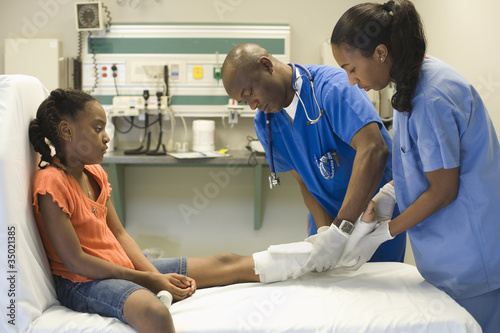 African American doctors treating girl's leg with bandages