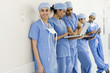 Asian surgeons leaning against wall in hospital