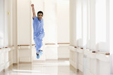 Asian doctor in scrubs jumping in corridor