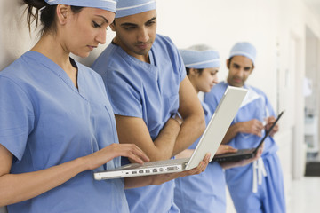 Asian surgeons using laptops in hallway