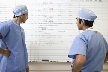 Asian surgeons looking at schedule in hospital