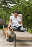 African American woman reading book and petting dog