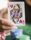 Hand holding queen of hearts playing card