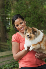 African American woman holding dog