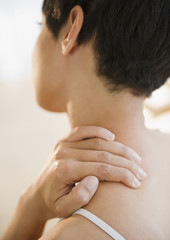 Mixed race woman rubbing neck and shoulder