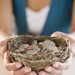 Mixed race woman holding nest filled with coins