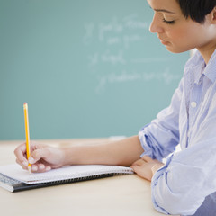 Mixed race woman writing in notebook