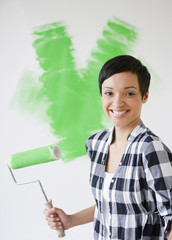 Mixed race woman holding paint roller with green paint