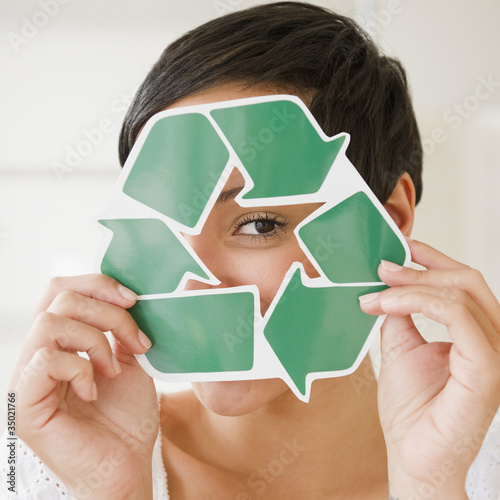 Mixed race woman holding recycling symbol in front of face