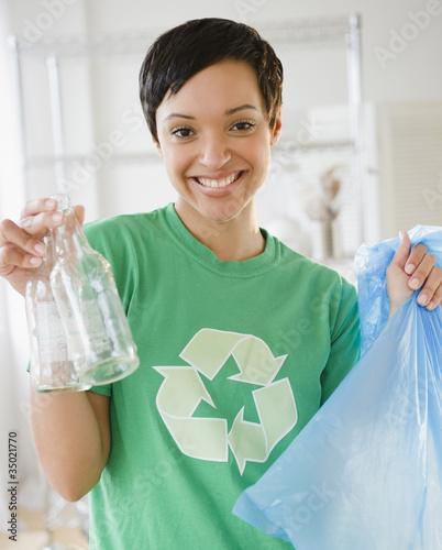 Mixed race woman recycling bottles