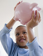 African American boy lifting piggy bank