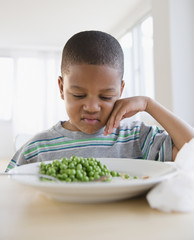 African American grimacing at plate of peas