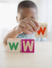African American boy spelling WWW with blocks