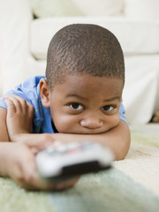 African American boy laying on floor watching television