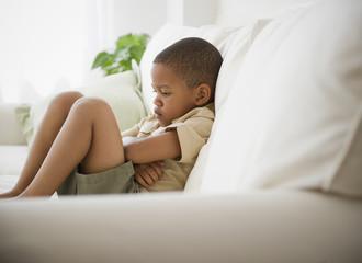 African American boy unhappy on sofa