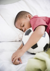 African American boy sleeping with soccer ball