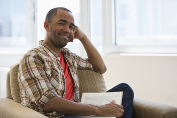 Mixed race man sitting in armchair reading book