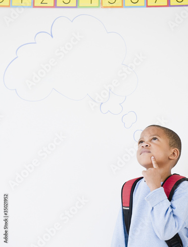 African American boy in school with thought bubble