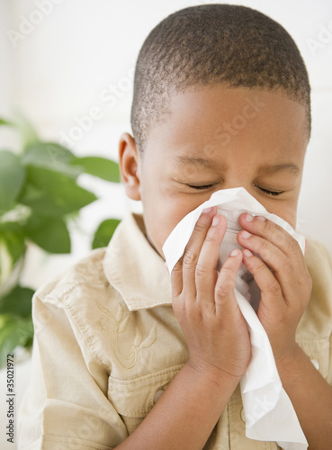 African American boy sneezing into tissue