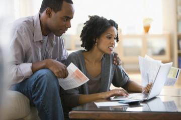 Couple paying bills using laptop