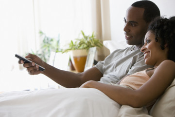 Couple laying in bed watching television