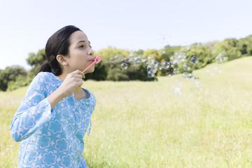 Hispanic girl blowing bubbles in field