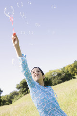 Hispanic girl making bubbles in field