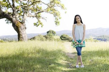 Hispanic girl standing in field