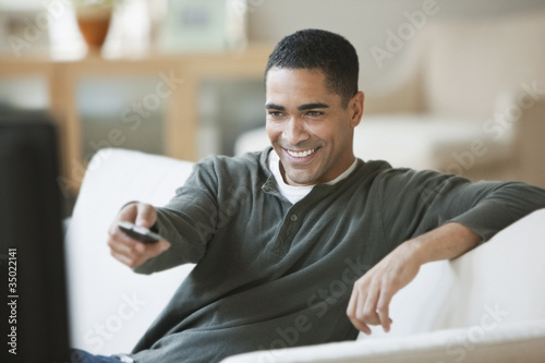 Mixed race man sitting on sofa watching television
