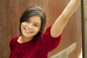 Smiling Hispanic woman leaning on metal pole